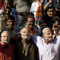 Masked hate?: Bharatiya Janata Party workers wearing masks of Gujarat state Chief Minister Narendra Modi show off victory signs in Ahmadabad, India, in December 2007. | BLOOMBERG