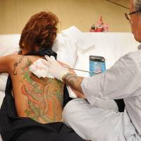 Master at work: Japanese tattooist Horiyoshii III tattoos a flower on the back of a woman. Traditional Japanese tattoos like this can be quite painful but perhaps not as painful as discovering the kanji you had inked on your skin doesn't mean what you thought it did! | AFP-JIJI
