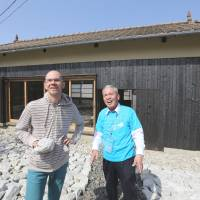 James Jack (left) talks with a volunteer in front of his 'SUNSET HOUSE: Language as the house of Being' at Shodoshima. | YURIKO NAKAO
