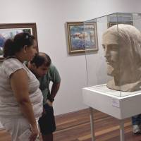 Allegorical: J.M. Coetzee's new novel bursts with philosophizing but isn't explicitly about Jesus. At right, visitors look at French sculptor Paul Landowski's original terra-cotta head from the famous Christ the Redeemer statue that towers over Rio de Janeiro at the newly opened Rio Art Museum in the Brazilian city on March 7. | BLOOMBERG