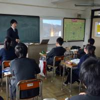 Distant learning: Junior high school students take a class at an ethnic Korean school in Yokohama, while an image of North Korea's rocket launch is projected on a screen. | AFP-JIJI