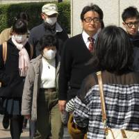 Smoke screen: Pedestrians wearing masks in Fukuoka Pref. on March 5. The local government has advised residents to stay indoors or wear masks when they go outside in the nation's first official health warning over smog drifting in from China. | AFP-JIJI
