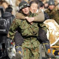 She ain't heavy: A member of the Japan Ground Self-Defense Force carries an elderly woman on his back as people are evacuated to a shelter at Kesennuma city in Miyagi Prefecture on March 12, 2011. Data collected during the initial stages of the 3/11 disaster could help focus such rescue efforts in future disasters. | AFP-JIJI