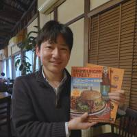 Beef boffin: Yoshihide Matsubara  holds up issues of Hamburger Street, his self-published magazine guide to the best burgers in Japan. His passion for patties has led to his guidebook 'The Burger Map,' media appearances. | REBECCA MILNER