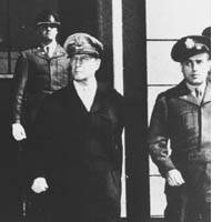 Glancing toward the Imperial Palace, Gen. Douglas MacArthur emerges from the Dai-Ichi Mutual Life Insurance Building in Tokyo.