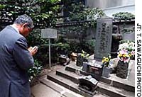 A visitor plays it safe by paying his respects at the burial mound reputed to contain the head of the 10th-century warrior Taira no Masakado.
