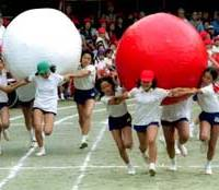 Teams of children race while carrying huge balls at a Tokyo elementary school's Sports Day.