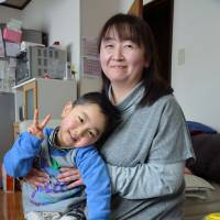Brave faces: Sachiko Inamura (with her 5-year-old son), struggles to pay the mortgage on the house she abandoned inside the Fukushima evacuation zone. | WINIFRED BIRD