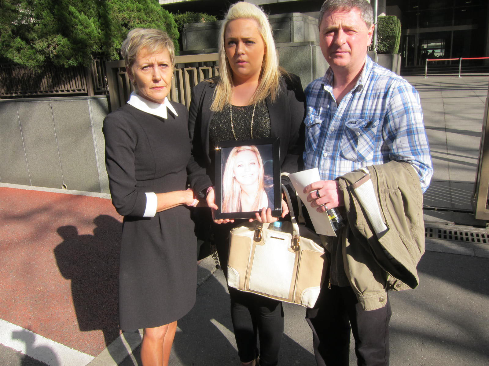 A family devastated: Andrea Furlong holds a picture of her late sister, Nicola, with parents Angela and Andrew outside the  Tokyo District Court.   DAVID MCNEILL