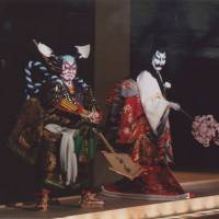 The ghost of Seigen, played by Nakamura Fukusuke IX holds out a branch of cherry blossoms as she is subdued by the warrior Awazu no Rokuro (Nakamura Kanjaku) in Act IV of 'Sumidagawa Hana no Goshozome' ('The Sumida River Adorned with Cherry Blossoms'). | COURTESY OF THE NATIONAL THEATRE OF JAPAN