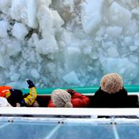 Ice blocks: Tourists lean out the Icebreaker Aurora II to better hear the haunting crush of drift ice as the ship grinds through. | ETHAN SALTER