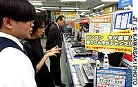 Customers browse by a sign reading, 'PC -- Now is your chance! Prices have hit rock bottom!' at a store in Shinjuku Ward, Tokyo.