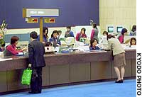 A clerk at Mizuho Bank helps a customer make a transaction as it handled the largest number of daily online transactions since its inauguration April 1.