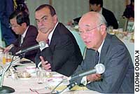 Mitsubishi Corp. Chairman Minoru Makihara speaks to a newly established forum of businesspeople at a Tokyo hotel, as Nissan Motor Co. President Carlos Ghosn looks on.