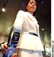 An employee at NTT DoCoMo Inc.'s future mobile service showroom in Tokyo demonstrates how a third-generation cell phone can be used to pass through ticket gates at transportation and other facilities.
