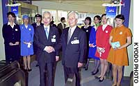 Japan Airlines President Isao Kaneko (left) and his Japan Air System counterpart, Hiromi Funabiki, celebrate the start of integrated operations at Tokyo's Haneda airport under the new holding company Japan Airlines System Corp.