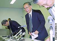 Akira Sakata, president of USJ Co., announces his resignation during a news conference in Osaka.