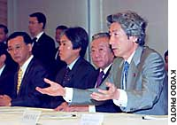 Prime Minister Junichiro Koizumi addresses a meeting Friday on regulation-free special economic zones, accompanied by Nobuteru Ishihara (left), minister in charge of administrative and regulatory reforms, and Yoshitada Konoike, minister in charge of disaster prevention.