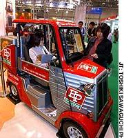 Visitors examine Mitsuoka Motor Co.'s ME2 electric delivery vehicle at the Tokyo Motor Show held at Makuhari Messe.