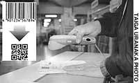 A warehouse employee scans a square symbol (inset) printed on an invoice at Mitsukoshi's distribution center in Tokyo's Koto Ward.