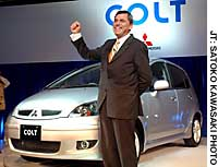 Rolf Eckrodt, CEO of Mitsubishi Motors Corp., shows off the new Colt compact during a media preview at a Tokyo hotel Monday.