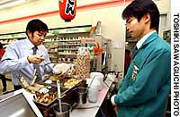 A Customer digs in to the 'oden' at a Seven-Eleven in Kamiyacho-ekimae in Tokyo's Minato Ward.