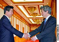 Prime Minister Junichiro Koizumi is greeted by South Korean President Roh Moo Hyun before their first bilateral summit at the presidential Blue House in Seoul.