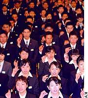 Newly hired employees of the supermarket chain Ito-Yokado Co. practice sign language at a Tokyo hotel before taking part in an entry ceremony.