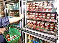A shopper examines shelves of premium ice cream at a FamilyMart convenience store in Tokyo's Toshima Ward.