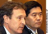 Donald Kanak, chief of the Japanese and South Korean operations of American International Group Inc., speaks at a news conference in Tokyo, as Yoshiaki Fujimori, head of the Asia-Pacific operations of the General Electric group, looks on.