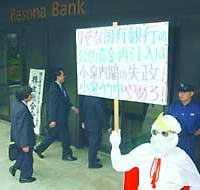 A man  dressed as a classic TV character displays a sign Friday criticizing Prime Minister Junichiro Koizumi's Cabinet for a planned capital injection to Resona Holdings Inc. outside the banking group's head office in Osaka.