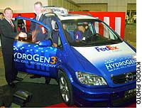 Raymond Grigg (left), head of General Motors Japan Ltd., turns over to David Ross, vice president of Federal Express Corp.'s North Pacific Region, a fuel-cell vehicle at the FedEx Ariake cargo distribution center in Tokyo's Koto Ward.