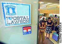 Customers shop in the new Postal Lawson outlet at the Yoyogi Post Office in Tokyo's Shibuya district.