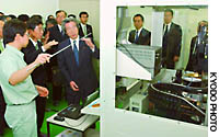 Prime Minister Junichiro Koizumi learns about state-of-the-art technology for analyzing gene information at Cluster Technology Co. in Higashiosaka, Osaka Prefecture, Wednesday.