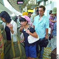Families board a Tokaido Shinkansen Line train at JR Tokyo Station as the annual outbound exodus for the Bon holiday peaks.