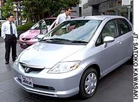 Businessmen check out a Honda Fit Aria sedan, which is manufactured in Thailand. The car was on display at the automaker's showroom in Minato Ward, Tokyo.