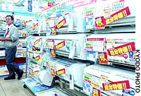 A sales clerk walks by rows of air conditioners marked with 'clearance price' stickers at an appliance store in Tokyo.