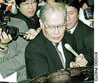 Daiei President Kunio Takagi is surrounded by reporters outside a Tokyo hotel Tuesday evening after meeting with the president of the Industrial Revitalization Corp. of Japan.