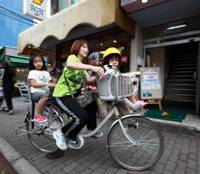 Easy rider: A woman pedals a battery-powered bicycle in Tokyo in July. | BLOOMBERG PHOTO