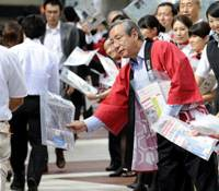 Down to earth: JAL President Haruka Nishimatsu, in happi coat, makes a sales pitch and hands out the struggling airline's leaflets to passersby Friday in Tokyo's Yurakucho district. | KYODO PHOTO