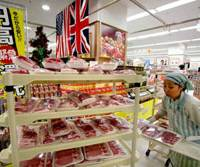 More on the table: A clerk prepares imported meat Tuesday for a 'high yen' sale at an Ito-Yokado supermarket in Tokyo. | BLOOMBERG