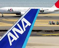 Archrivals: A Japan Airlines Corp. jetliner passes by an All Nippon Airways Co. plane parked at Haneda airport in Tokyo in January 2008. | BLOOMBERG