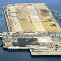 Connection: A man-made island to accommodate a new runway at Haneda airport in Tokyo is attached to the main airport island Wednesday. The runway is scheduled to open in October.   KYODO PHOTO