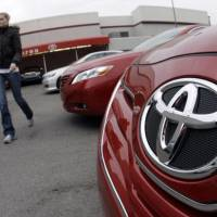 Uncertain times: A woman walks past a new 2010 Toyota Camry at a dealership in Nashville, Tenn., on Wednesday. | AP