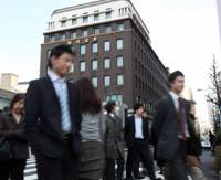 On the move: People walk by the Nomura Securities headquarters building in Chuo Ward, Tokyo, in January 2009.   BLOOMBERG