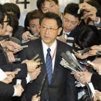 Damage control: Toyota Motor Corp. President Akio Toyoda faces reporters Tuesday in Tokyo after reporting to transport minister Seiji Maehara on the firm's plans to recall about 400,000 hybrid cars around the globe. | KYODO PHOTO
