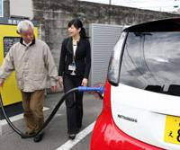 Juice her up: Chitoshi Okunuki is taught how to use the high-speed battery charger for Mitsubishi Motors Corp.'s electric car i-MiEV at an MMC showroom in Tokyo Thursday. | AP PHOTO
