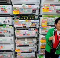 Pitchman: A Bic Camera salesclerk speaks in front of energy-saving air conditioners in Tokyo last May.   AP PHOTO