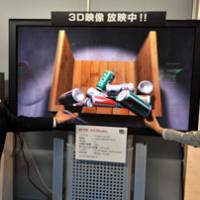 Can't believe it: YMJ Inc. employees introduce the firm's 65-inch 3-D display that doesn't require special glasses at a display fair at Tokyo Big Sight on Wednesday. | YOSHIAKI MIURA PHOTO