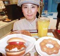 Diet buster: An employee at a Mosdo fast-food restaurant in Fuchu, Hiroshima Prefecture, shows off a combo set featuring a hamburger from Mos Burger and a doughnut from Mister Donut on Tuesday.   KYODO PHOTO